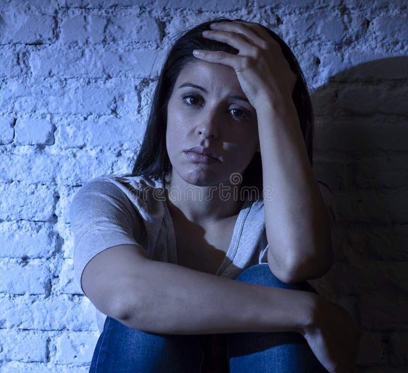 坐地板的孤独的年轻可爱的西班牙妇女在家挫败了感到遭受的消沉哀伤和绝望与头 免版税库存照片