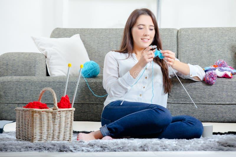 坐地板编织的女孩 库存照片