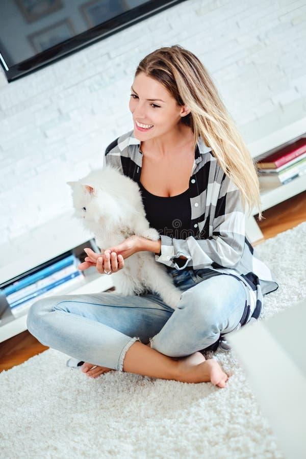 坐地毯和使用与波斯猫的女孩 免版税库存图片