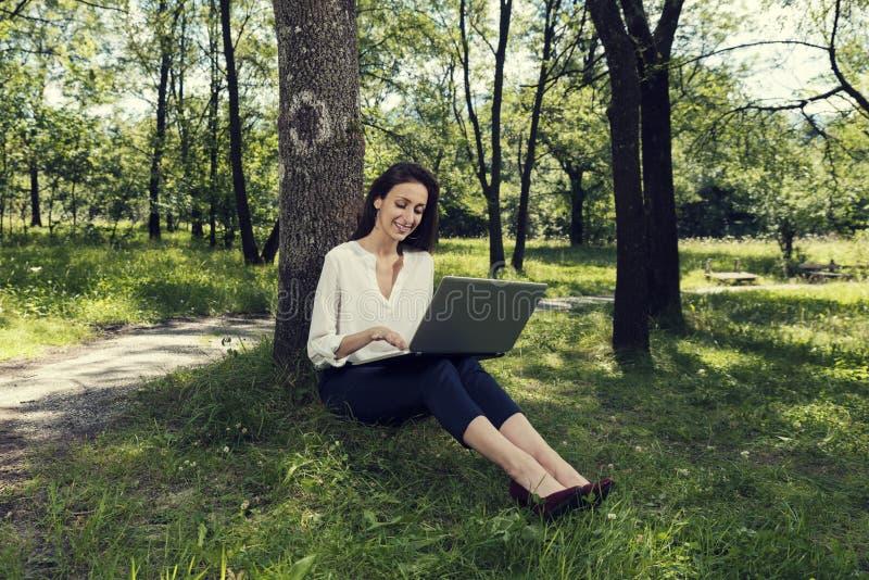 坐地面和研究她的膝上型计算机的年轻女商人在一公园和微笑 免版税库存照片