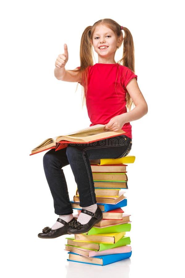 坐堆书和显示赞许的愉快的小女孩 免版税图库摄影
