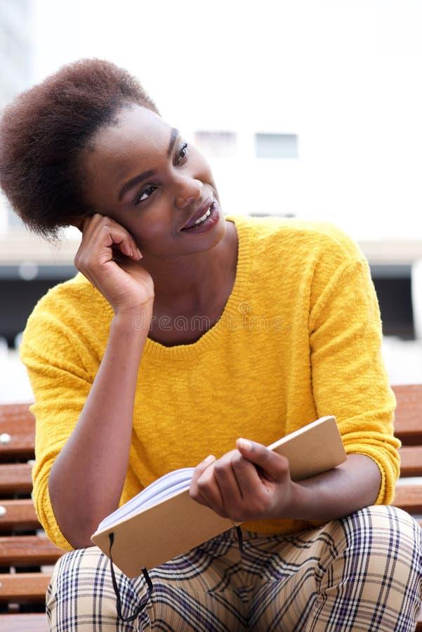 坐外面与书和认为的非裔美国人的妇女 免版税图库摄影