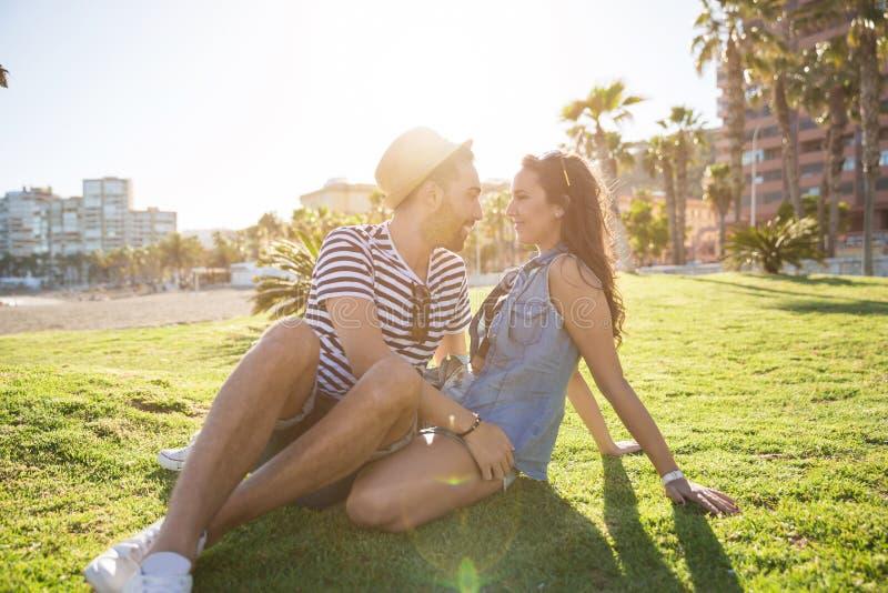 坐外面与女朋友的年轻人谈话与她 免版税库存图片