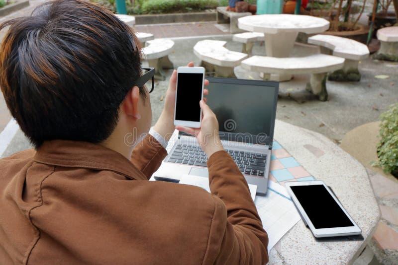 坐大理石椅子和读消息的商人在他的流动智能手机在公园 免版税库存照片