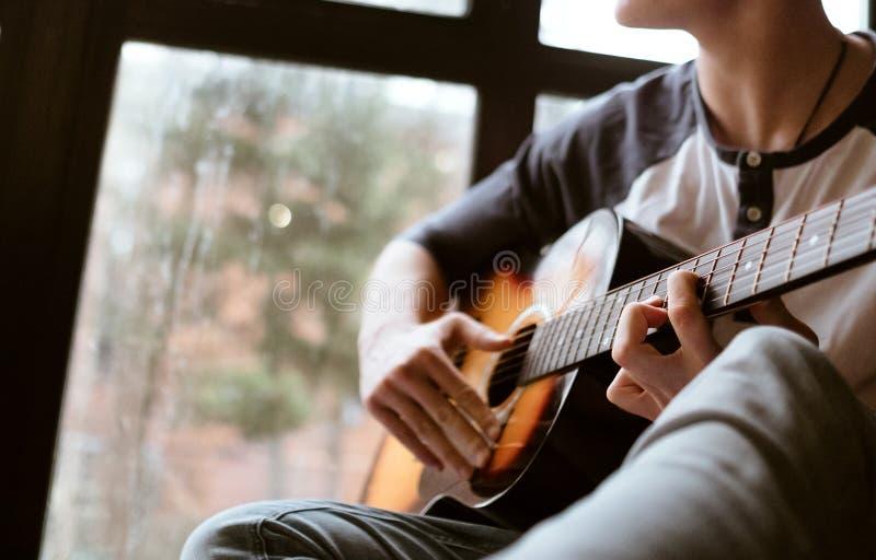 坐大窗口windowsil和使用在吉他-手指的人手接近图象 免版税库存照片