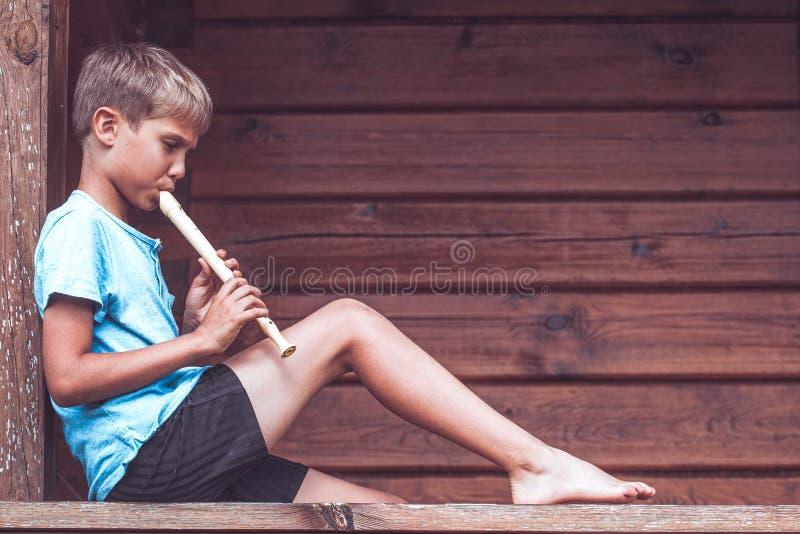 坐大阳台和演奏长笛的男孩户外 免版税图库摄影