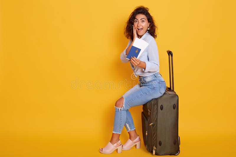 坐她的大手提箱和持与机票的激动和愉快的年轻快乐的女性游人护照,穿戴  库存图片