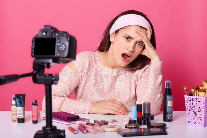 坐对桃红色墙壁的美丽的年轻白种人妇女接近的画象,在照相机前面,看起来疲乏和困, 免版税库存图片