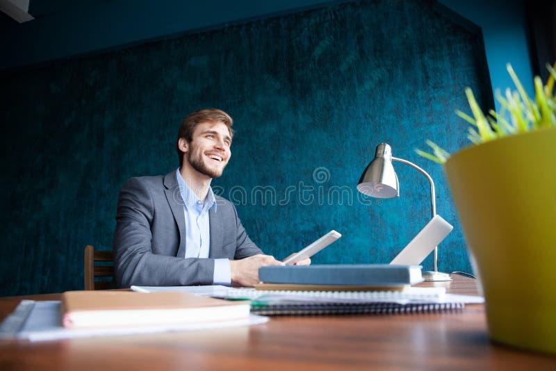 坐射击年轻的人在看起来的桌去和认为 坐在办公室的周道的商人 免版税库存图片
