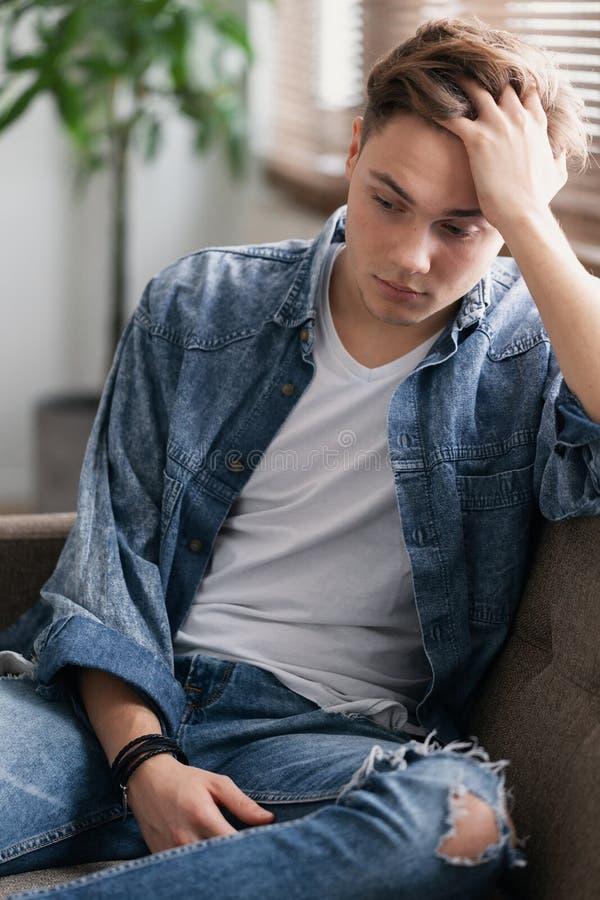 坐少年的学生在家单独等待他的父亲 图库摄影