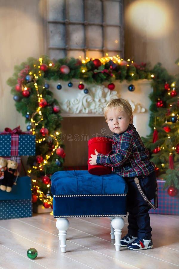 坐屋顶在装饰的演播室和使用与圣诞礼物和箱子的小白肤金发的男孩画象  装饰  免版税库存照片
