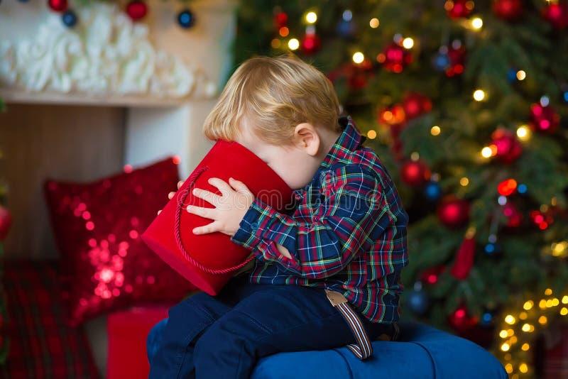 坐屋顶在装饰的演播室和使用与圣诞礼物和箱子的小白肤金发的男孩画象  装饰  库存照片