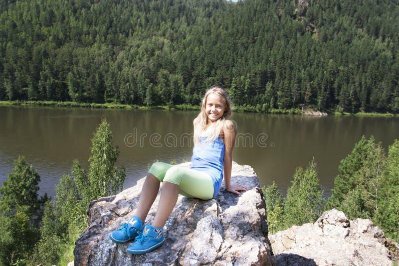 坐岩石和享受河视图的女孩 免版税库存照片