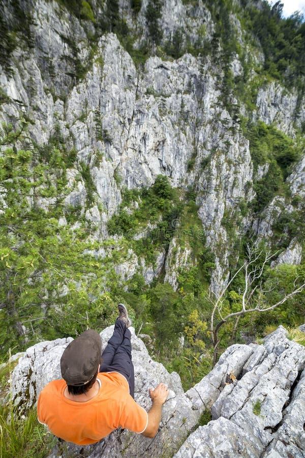 坐岩石和敬佩看法的远足者年轻人 免版税库存照片