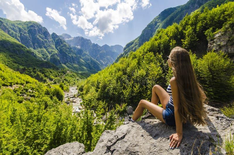坐岩石和看美丽的山的少妇 库存图片