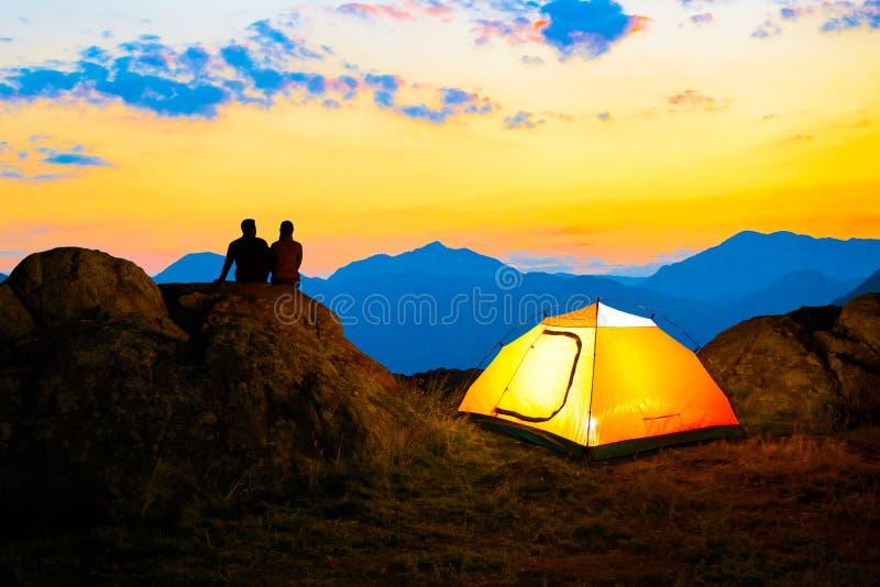 坐岩石在有启发性帐篷附近和观看与日落天空的年轻夫妇美好的晚上山景城 免版税库存照片
