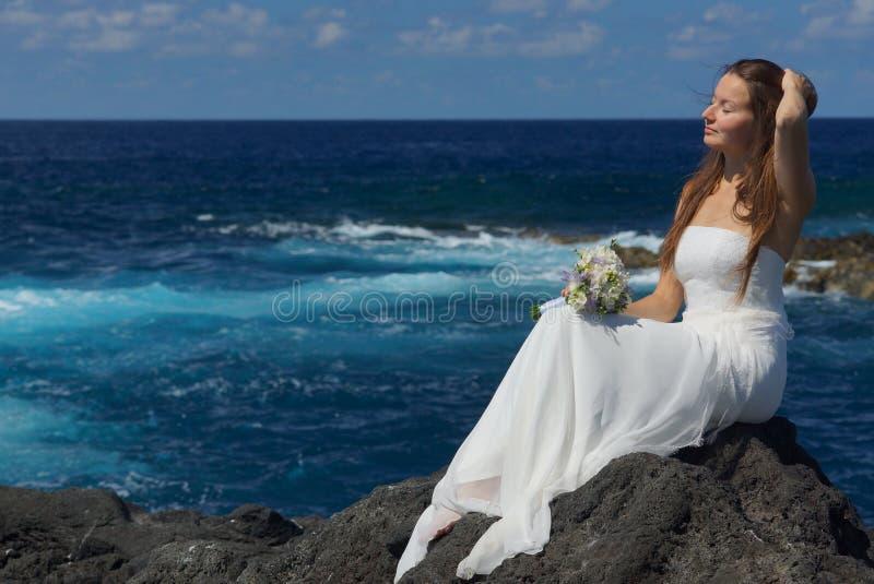 坐岩石岸和看海洋的白色婚礼礼服的年轻未婚妻在圣地米格尔海岛,亚速尔群岛 免版税库存图片