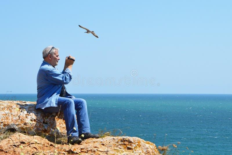 坐峭壁高在看见灰发的人上拍摄seagulls'飞行的录影 免版税库存照片