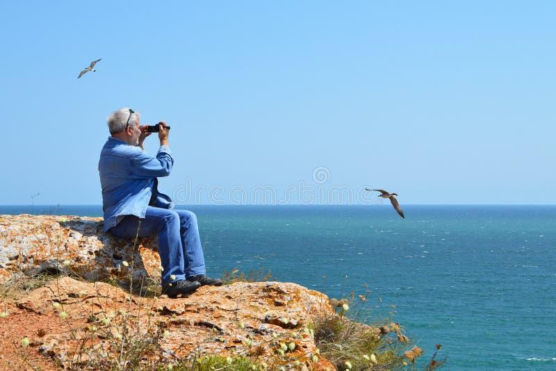 坐峭壁高在看见灰发的人上拍摄seagulls'飞行的录影 库存图片