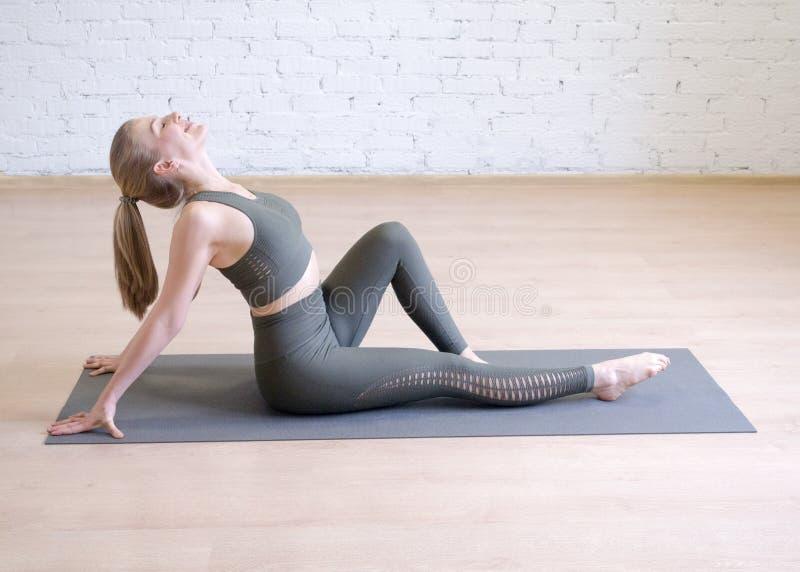 坐席子和弯曲她的后面的灰色体育穿戴的可爱的妇女在瑜伽演播室,选择聚焦 库存图片