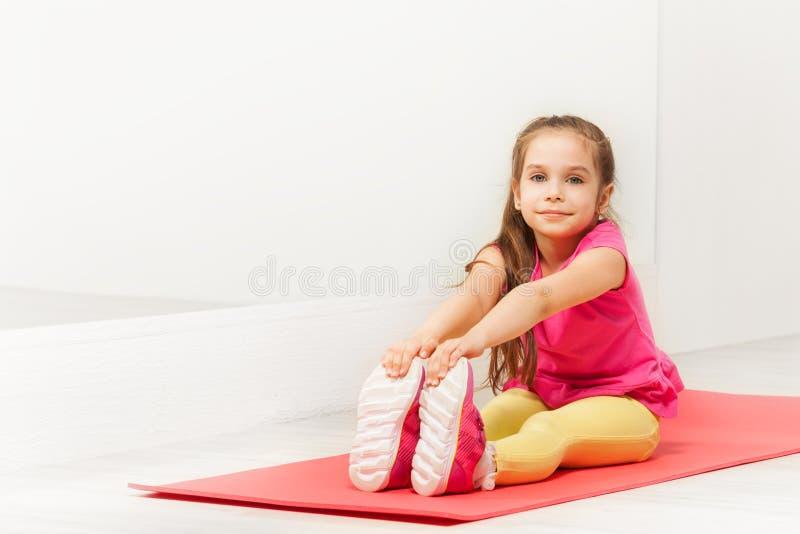 坐席子和舒展腿的年轻体操运动员 库存图片
