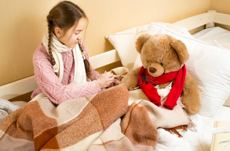 坐床和做射入的女孩变褐玩具熊 库存图片