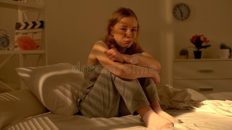 坐床和哭泣在绝望,青春期消沉的孤独的十几岁的女孩 库存图片