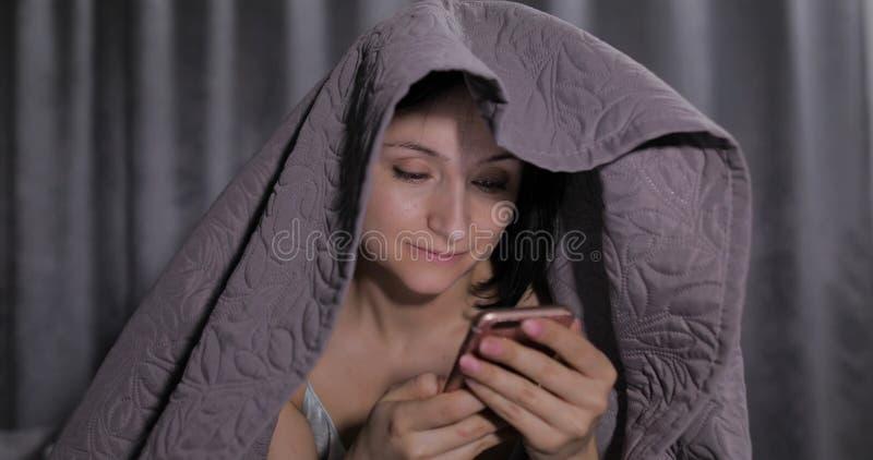 坐床在毯子下和享受聊天的妇女对朋友在智能手机 库存图片