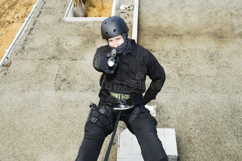 坐式下降法和瞄准枪的特警队官员 库存图片