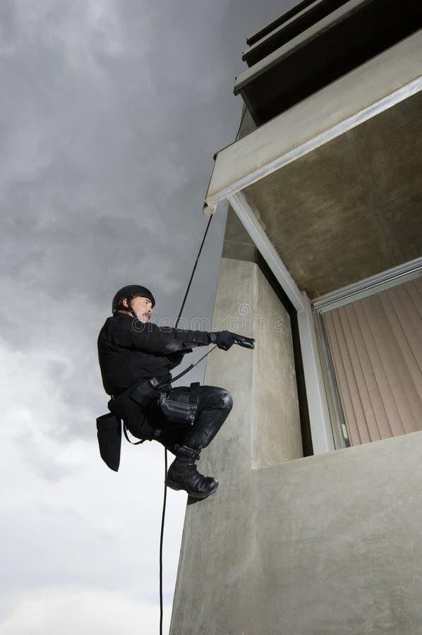 坐式下降法和瞄准枪的特警队官员 免版税库存照片
