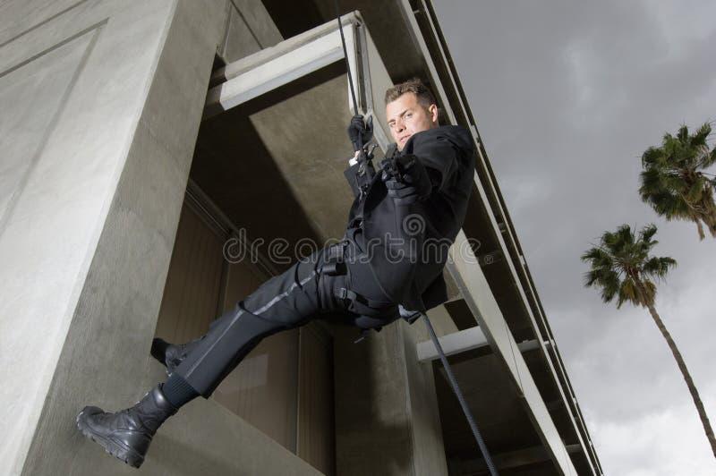 坐式下降法和瞄准枪的特警队官员 免版税库存图片