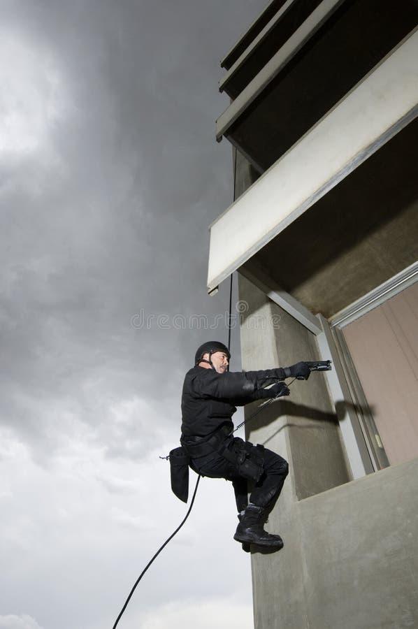 坐式下降法和瞄准枪的特警队官员 免版税图库摄影