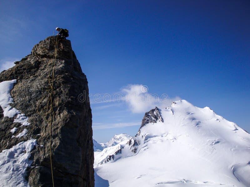 坐式下降法在一个被暴露的山土坎的一根锋利的岩石针的登山者在天空蔚蓝下 图库摄影