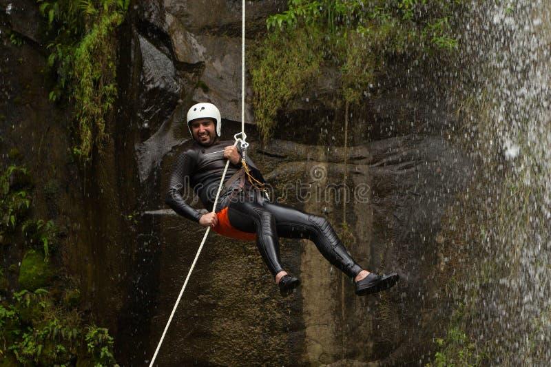 坐式下降法在峡谷冒险的瀑布 库存图片
