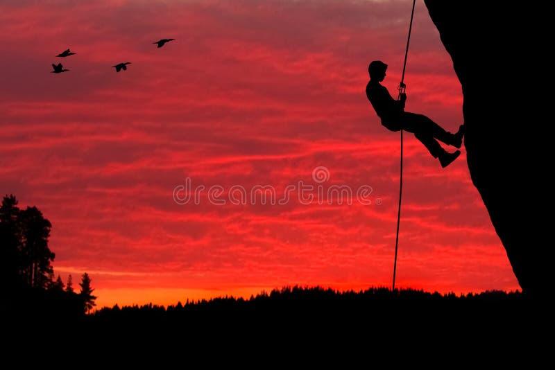 攀岩运动员坐式下降法的剪影 免版税库存图片