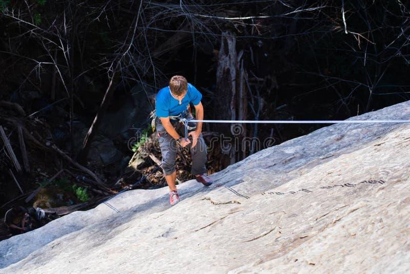 坐式下降法在攀登的登山人岩石墙壁以后 免版税库存图片