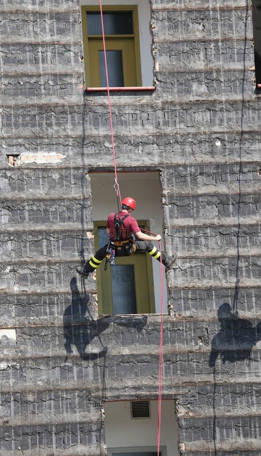 坐式下降法墙壁在消防训练期间的登山人消防队员 免版税库存图片