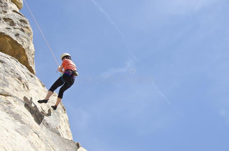 坐式下降法的攀岩运动员 库存照片