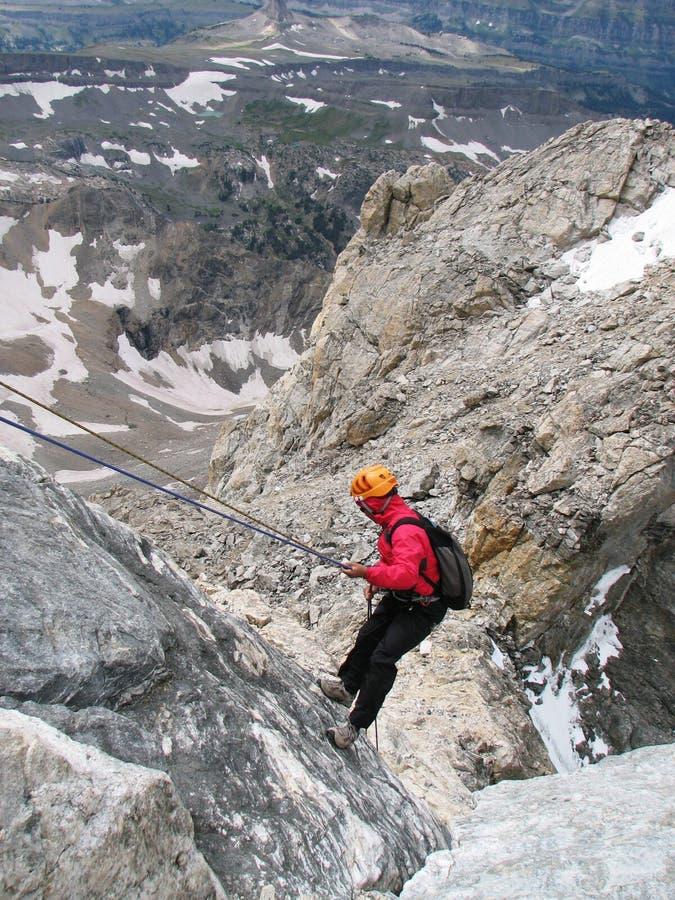 坐式下降法的登山家 免版税库存图片