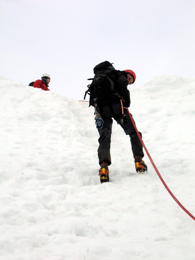 坐式下降法的登山家 图库摄影