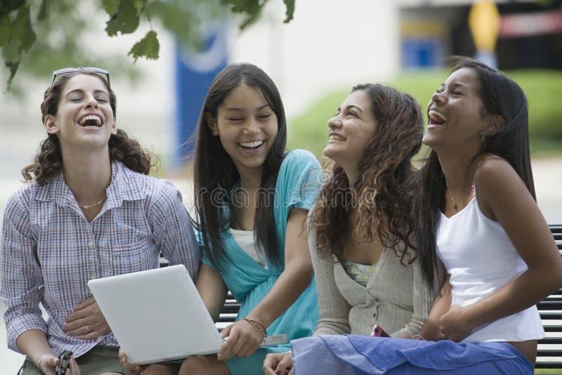 坐微笑的四个女孩少年 库存图片