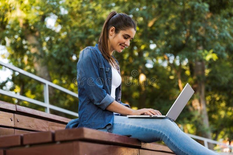 坐户外使用手提电脑的令人惊讶的年轻美女 免版税图库摄影