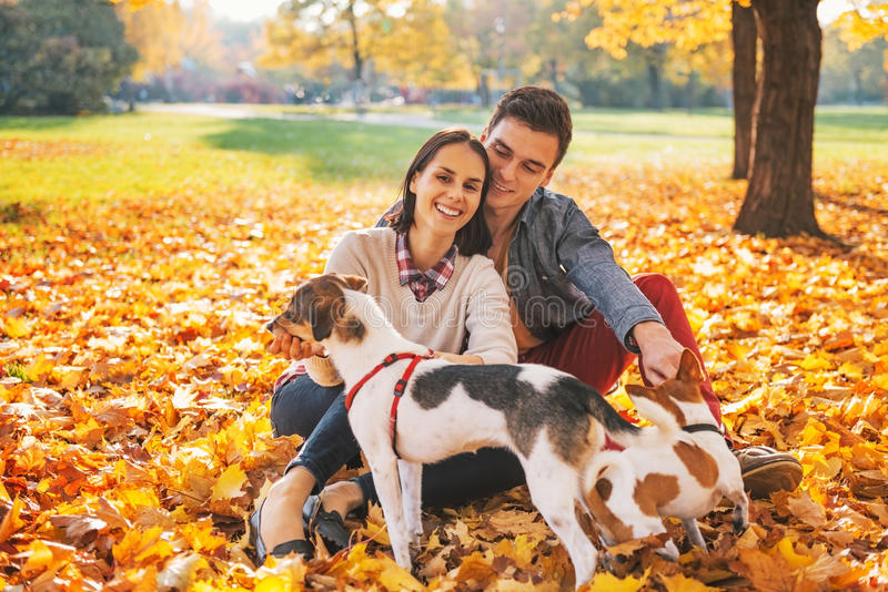 坐户外和使用与狗的愉快的年轻夫妇画象  库存照片