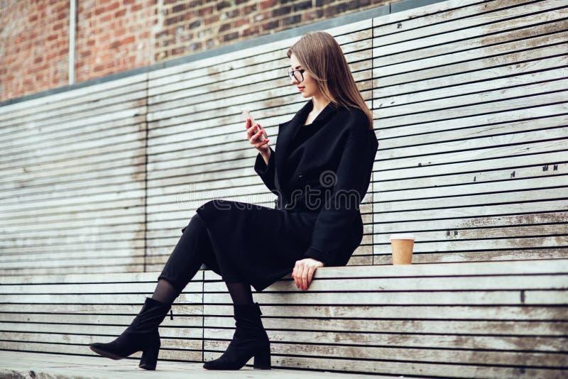坐户外和发短信在她的电话饮用的咖啡的愉快的微笑的妇女 免版税库存图片