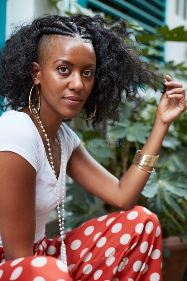 坐户外和接触她的头发的年轻黑人妇女 库存图片