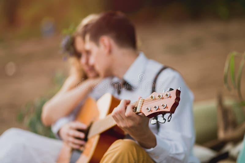 坐户外在与弹吉他的人的日落的浪漫夫妇 库存图片