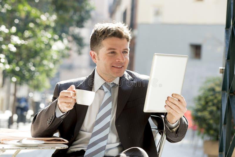 坐户外在咖啡休息的商人拿着检查onlï ¿ ½ ne新闻的杯子和数字式片剂垫 库存照片