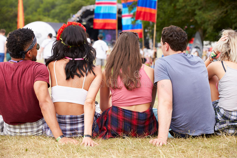 坐户外在音乐节,后面看法的青年人 免版税库存图片