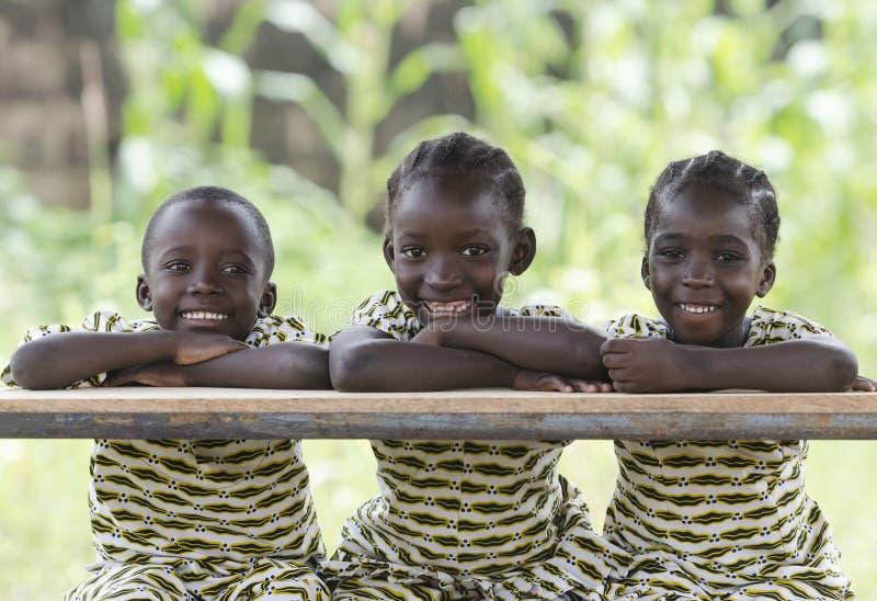 坐户外微笑和笑的三个非洲孩子 免版税库存图片
