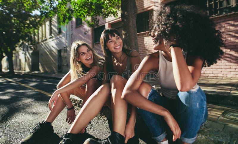 坐户外由路的三个美丽的女孩 免版税库存图片